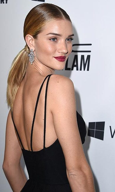 Model Rosie Huntington-Whiteley's take on the smooth look, this time paired with sparkling chandelier earrings and bold berry lips. 