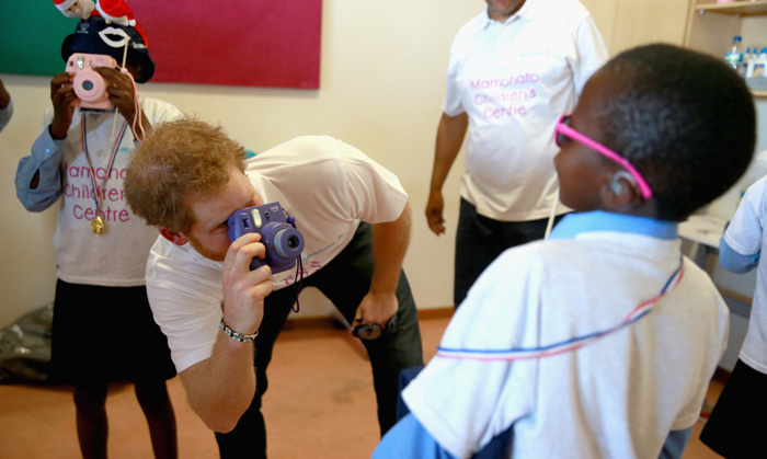 Snapped! Harry gets involved with the center's photography workshop taking pictures and posing with the young children.