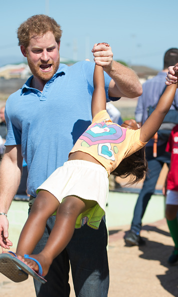 Prince Harry lifted 4-year-old Sinentlantla Jacobs during a visit to Football For Hope Centre in Khayelistsha in Cape Town, South Africa.