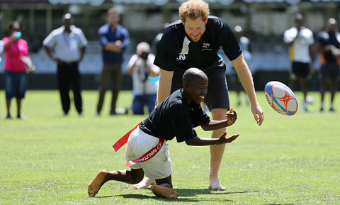 Prince Harry went barefoot to play some touch rubgy with  children at Kings Park Stadium along with players on The Sharks rugby team in Durban.