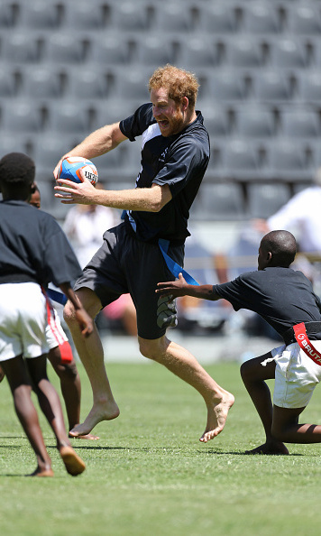 On the go! Prince Harry tried to escape the opposing team during a tag rugby game in Durban.