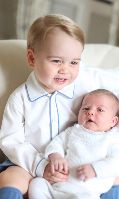 June 2015: The two-year-old was beaming as he cuddled his newborn sister Princess Charlotte.