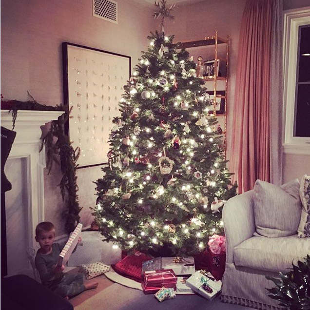 It looks like someone is trying to open up presents a little early underneath Reese Witherspoon's festive tree. 