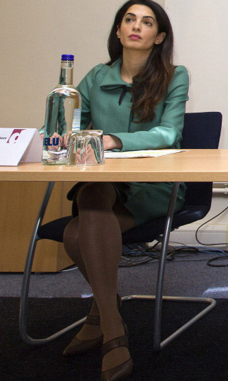 Even though she is sitting down, her style still shows.  Amal worked the board room in green, paired with brown shoes during a press conference in London. 