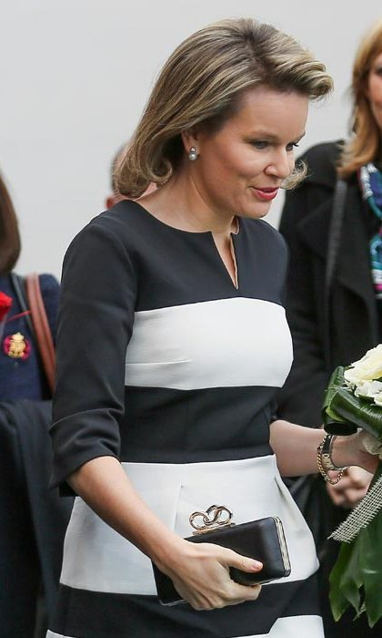 A box knuckle clutch complements Queen Mathilde of Belgium's bold monochrome stripes.
