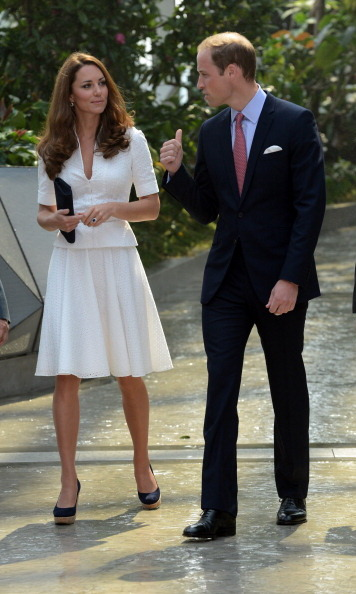 Kate looks every bit the professional in this white two-piece outfit while sharing a look with William. 