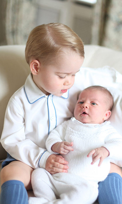 The tot looked every inch the proud big brother as he gazed down at his little sister.