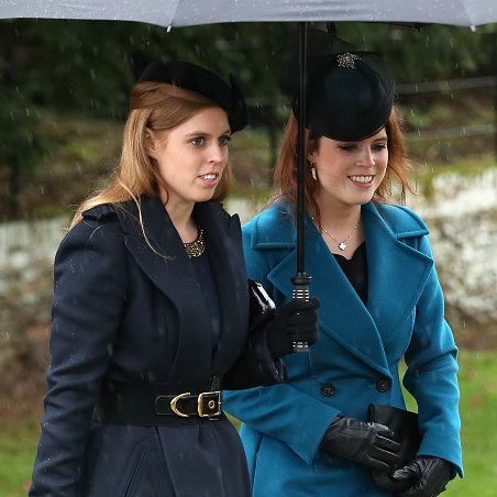 December 2015: An umbrella for two! Beatrice and Eugenie stuck close together as they made their way into church on Christmas.