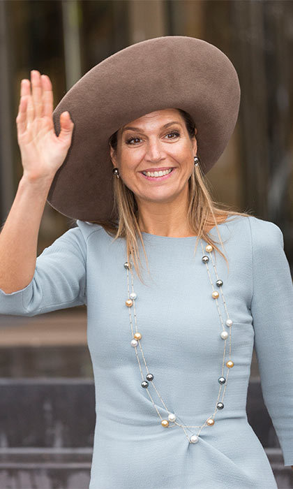 Queen Maxima broke up the high neckline of her light blue dress by adding a beautiful string of different-colored pearls.