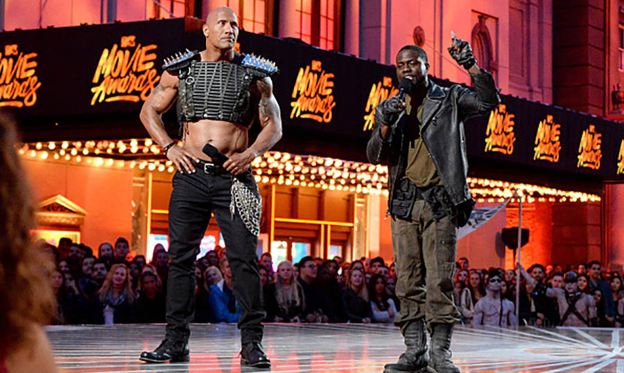 Talk about an entrance! Hosts Dwayne 'The Rock' Johnson and Kevin Hart kicked off the 2016 MTV Movie Awards with a <i>Mad Max</i> tribute, complete with fire and war boys. 