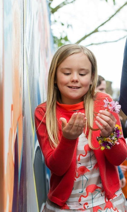 The Dutch King's youngest daughter, Princess Ariane, appeared fascinated by a pink flower, while out celebrating her father's 49th birthday.