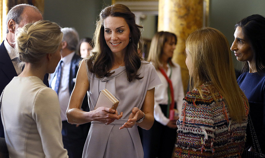Holding her box clutch in hand, she chatted with guests at the gathering. 