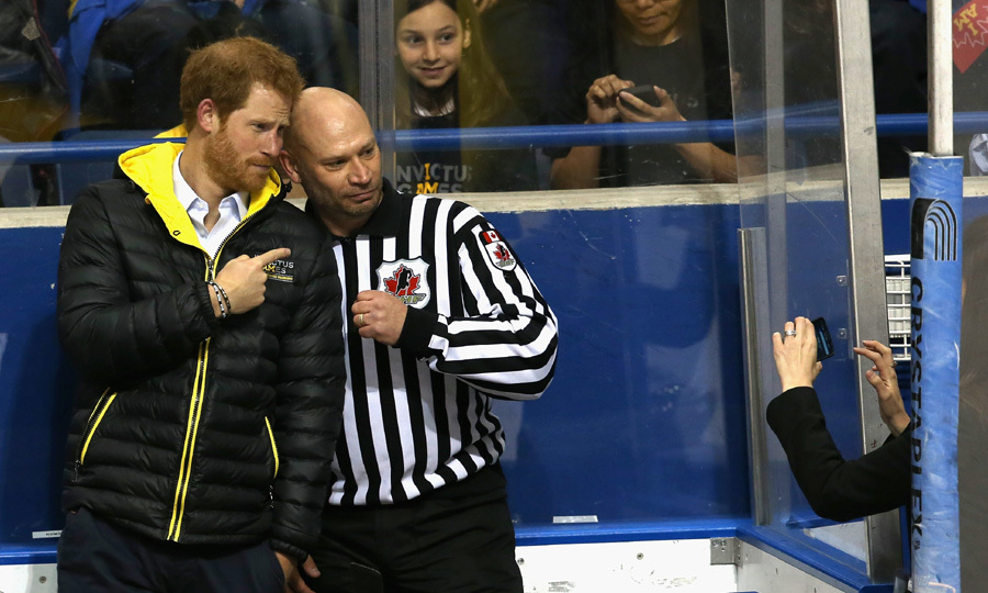Strike a pose! Prince Harry takes a photo with the referee as he watches a hockey match at the Athletic Center in Toronto.