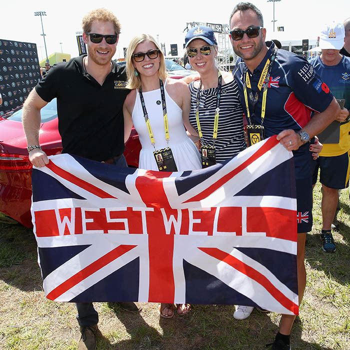 Let the games begin! Harry held up the flag with pride and posed with some British supporters during the Jaguar Land-Rover Driving Challenge.