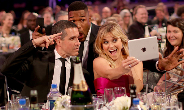 Who needs an iPhone when you've got an iPad?! Reese Witherspoon and husband Jim Toth were photobombed by Michael Strahan at the 20th annual Critics' Choice Movie Awards.
