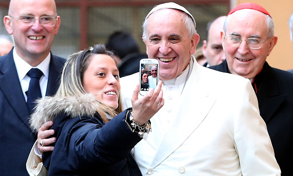 Pope Francis posed for a photo while visiting the Roman parish of St. Michael the Archangel in Pietralata.