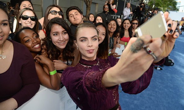 Say cheese! Cara Delevingne gave a silly face taking a photo with fans at the 2015 MTV Movie Awards in Los Angeles.