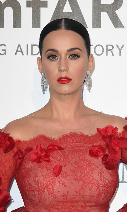 Katy Perry sizzled in a scarlet red gown at the amfAR gala, complementing the look perfectly with a matching statement red lipstick, her brunette tresses slicked back into a low ponytail to show off her dazzling earrings.