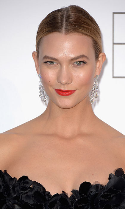 Karlie Kloss majorly upped the beauty stakes with this striking shade of red lipstick with coral undertones, flawlessly groomed brows and an elegant hairdo.