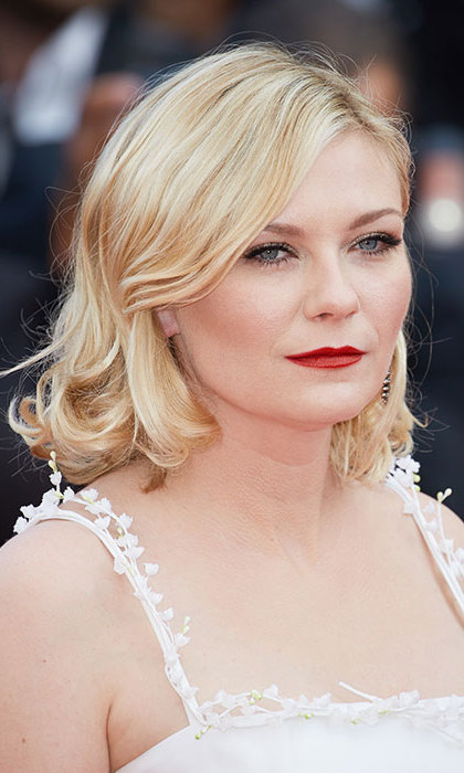 Kirsten Dunst looked every inch a blonde bombshell with her hair worn down in loose curls, paired with statement red lips and winged eyeliner for classic red carpet beauty.