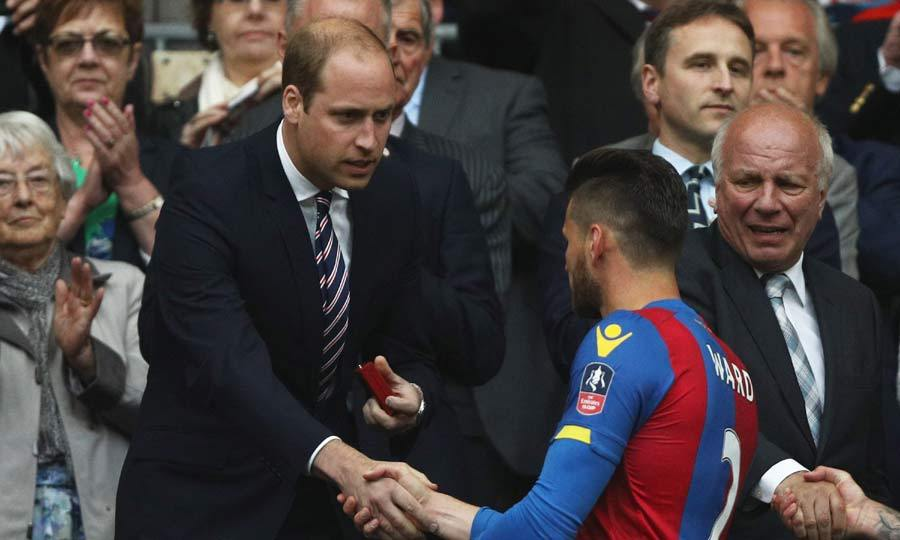 Consoling a Crystal Palace soccer player after his team lost the FA cup final to Manchester United, Prince William shook hands with the losing team and presented them with their runners-up medals.