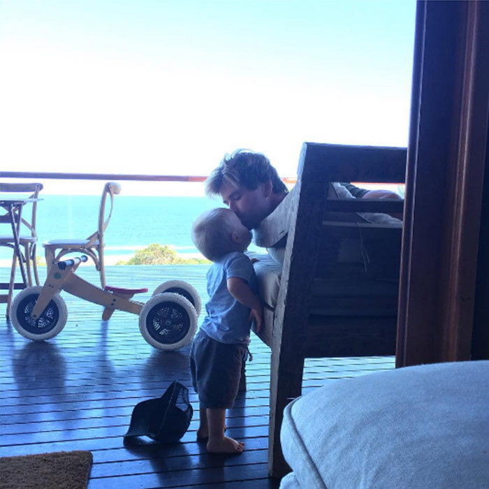 "Aaaaw! The couple's son Tristan got a quick kiss from dad while the pair chilled out on their balcony overlooking the ocean. Elsa perfectly summed up how we are all feeling, when she captioned this picture: ""I'm melting!!""