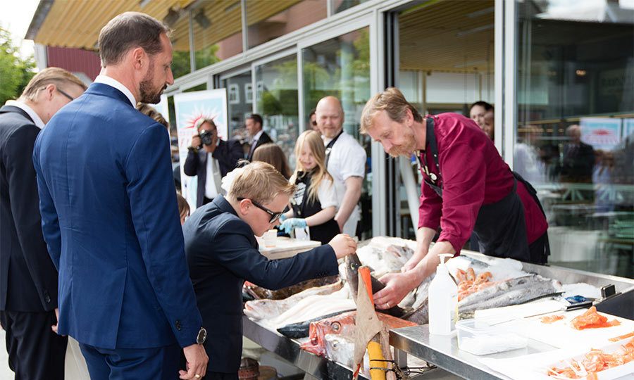 Curious about the fish, Prince Sverre Magnus had a closer look at the local catch of the day while talking to a local fisherman.