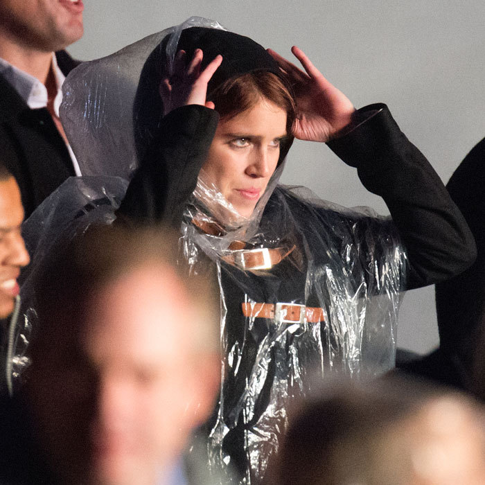 Eugenie covers up from the rainy British weather.