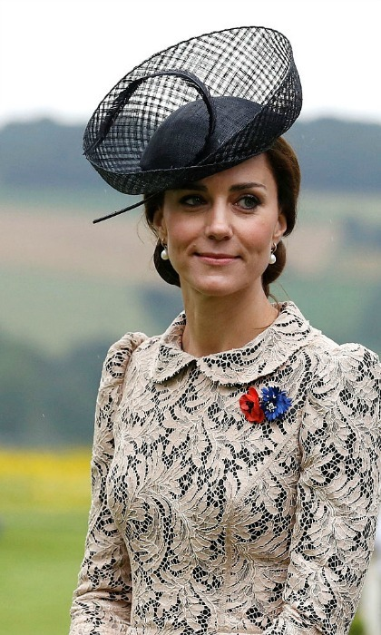 The Duchess completed her elegant look by tying her glossy locks into a low chignon and accessorizing with a black hat from Lock and Co and a pair of pearl drop earrings.