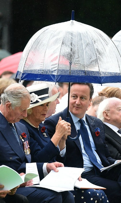 Camilla, the Duchess of Cornwall, shielded herself from the rain under her umbrella at the centenary commemoration, beside her husband Prince Charles and Prime Minister David Cameron.