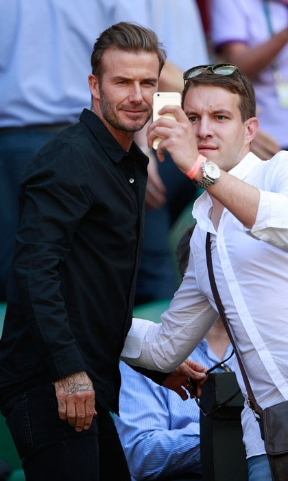 "Fashion campaign shoot or selfie? <a href=""https://us.hellomagazine.com/tags/1/david-beckham"" target=""_blank"" style=""font-weight: bold;"">David Beckham</a> looked as suave as ever posing for a snap with a fan at Wimbledon.