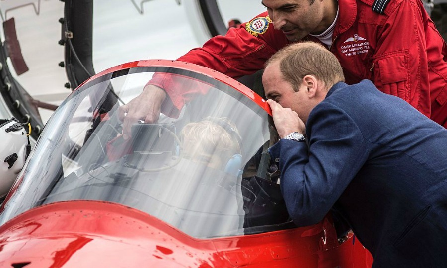 Ready for take-off! George was gearing up to take flight as he sat in the aircraft's cockpit with his dad looking on.
