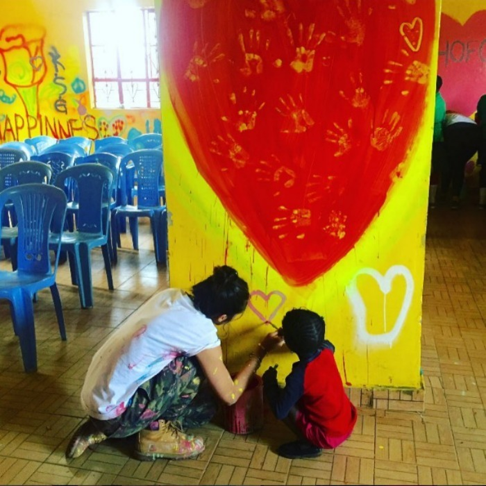 Lourdes spent some time painting the wall at an all girls primary school in Kibera with a young student named Beyonce. 
