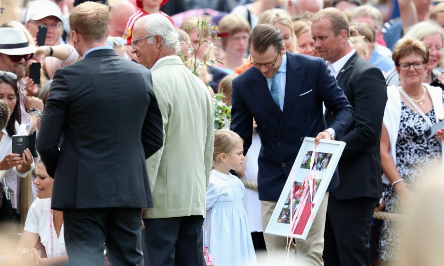 While guests presented Princess Victoria with gifts such as food, flowers and photographs, Princess Estelle was standing by to help her mother carefully collect them. 