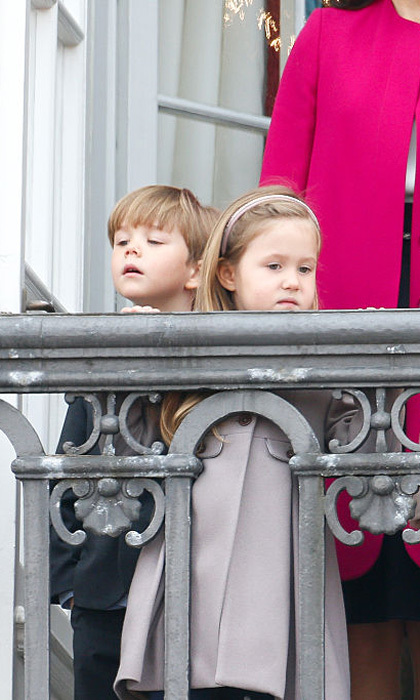 The royal duo peered over the balcony at Amalienborg Royal Palace for their grandmother's 76th birthday celebrations.