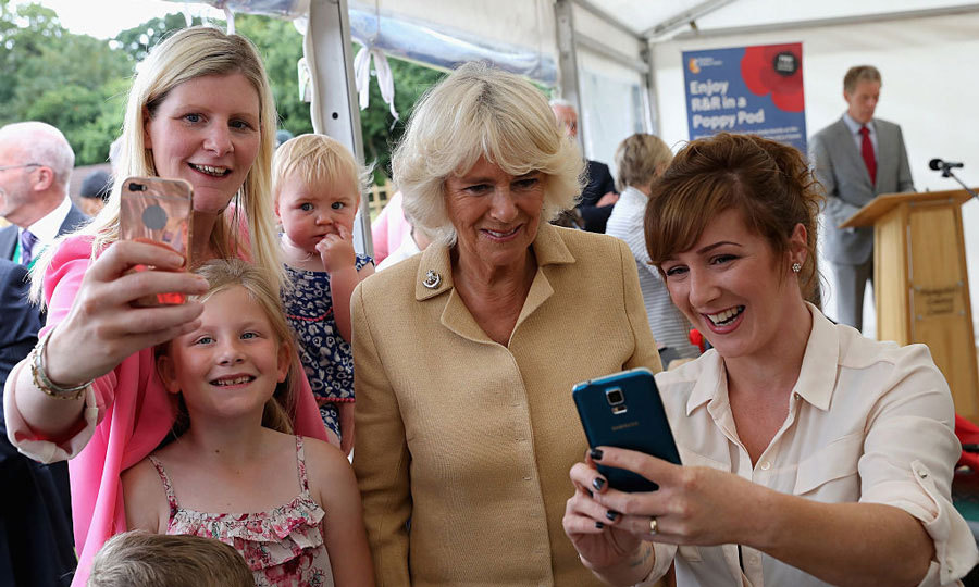 Double the selfie, double the fun! The Duchess of Cornwall posed for two photos at once during her visit to Poppy Pod Village at the Tile Barn Outdoor Centre.