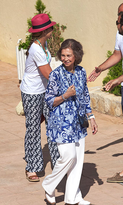 Queen Sofia of Spain looked casual in white linen trousers and a bold blue blouse as she enjoyed a day out.