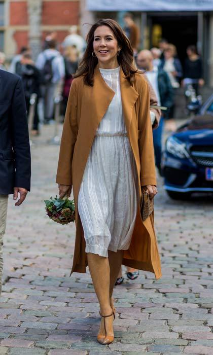 Princess Mary of Denmark looked stunning in a long white dress and brown coat, accessorizing with a pair of brown Mary Jane heels.