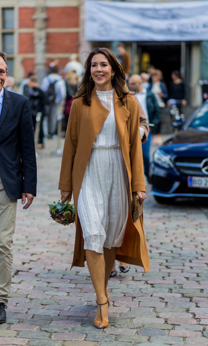 Crown Princess Mary of Denmark made a stylish appearance wearing a bespoke dress and camel coat for the first day of Copenhagen Fashion Week.