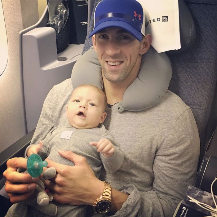 Homeward bound! After sweeping up six new Olympic medals in Rio, Michael headed back to the states with his happy baby boy on his lap.