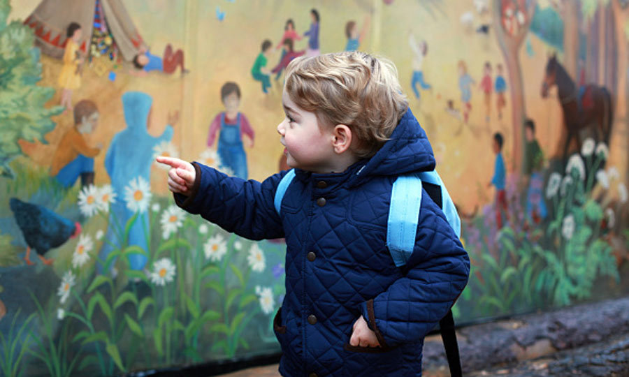 The royal toddler, who was taken to school by both mom and dad, admired a mural outside of Westacre Montessori in Norfolk.