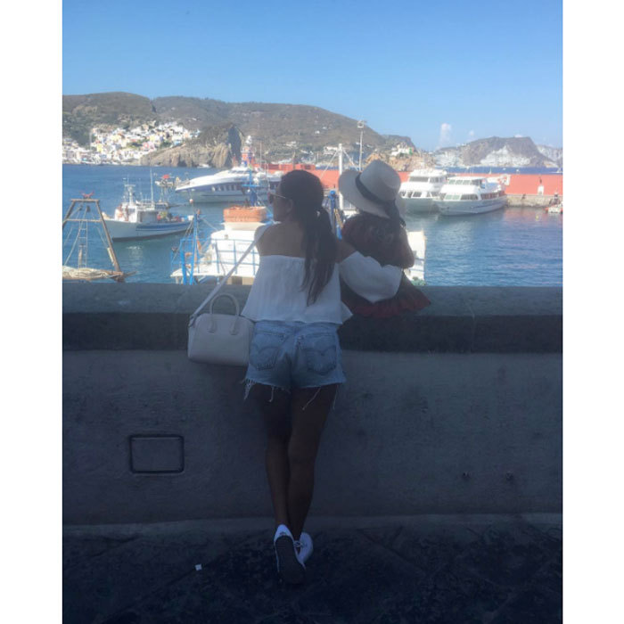 "The reality star stole a quiet moment with her daughter Penelope Disick, looking at boats in Italy. The mom-of-three captioned the photo, ""Tourists in Ponza.""