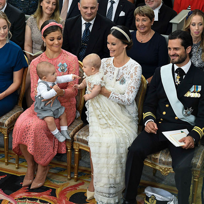 Prince Alexander shared an adorable moment playing with his cousin Prince Oscar (seated on his mom Crown Princess Victoria's lap) during his christening ceremony.