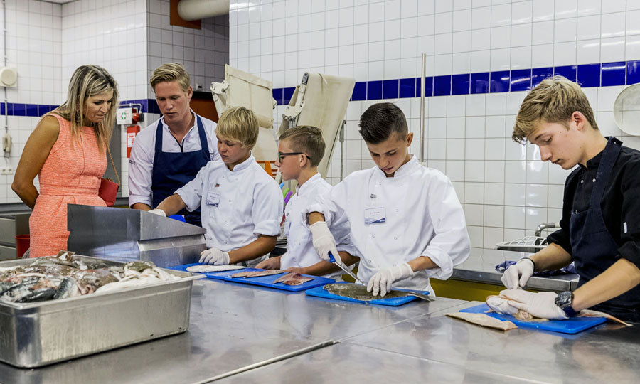 It was back to school for Queen Maxima of the Netherlands! The monarch looked on at children cutting fish, while visiting the Pontes Pieter Zeeman school in Zierikzee. 