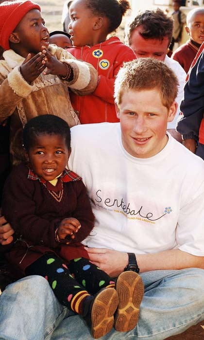 Prince Harry held a small girl during a 2006 trip to the Good Shepherd home, while visiting Lesotho, where he launched his charity 'Sentebale' that means 'Forget me not' in memory of his mother Princess Diana.