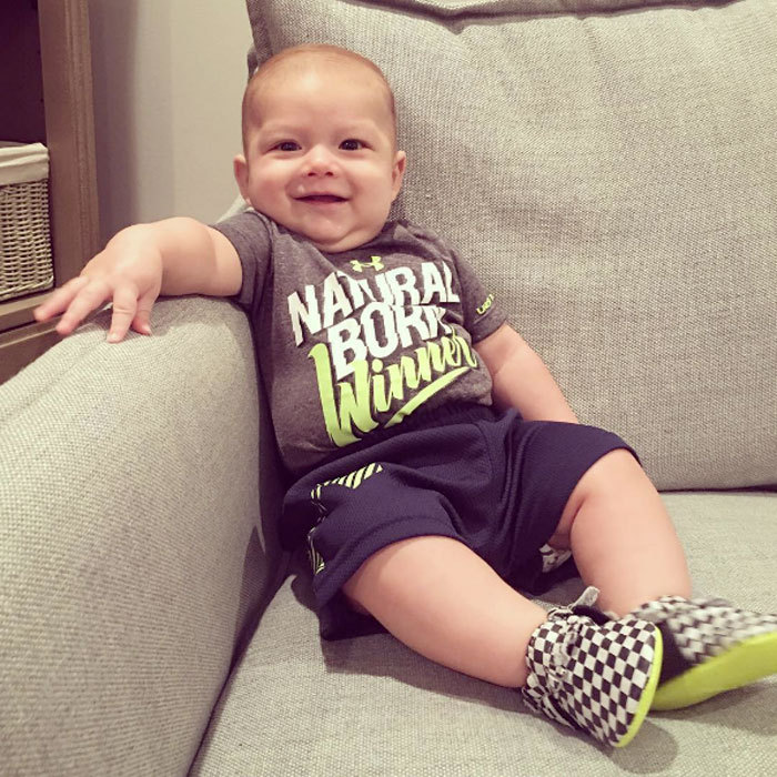 "A winning smile! Boomer sat perched up on a couch wearing a shirt that had the phrase ""Natural Born Winner"" printed on the front. Nicole shared the picture of her baby boy writing, ""Check out our smiley lil man this am! @m_phelps00.""