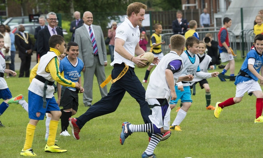 Catch me if you can! Harry got on the field and gave the children a run for their money during his coaching session at the Prince's Trust Team program in eastern England in 2014. 