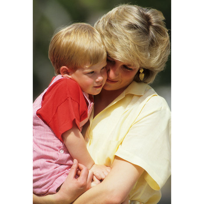 Prince Harry cuddled close to his doting mom, the Princess of Wales, while on holiday in 1987 in Majorca, Spain.