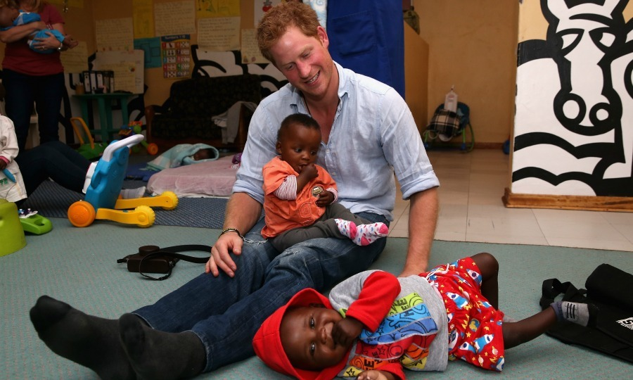 Tickle time! Prince Harry played with two children during his visit to Maseru, Lesotho in 2014.