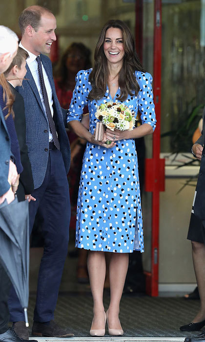 "Despite the rain, the Duchess of Cambridge looked sunny donning a label she has never worn before: Altuzarra. The mom-of-two showed off her trim figure wearing the label's blue polka-dot ""Aimee"" button-front dress, which features a V-neckline and slit. Kate accessorized the school look with a pair of tan heels and a matching clutch bag. 